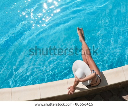 Young woman sitting on the ledge of the pool. - stock photo