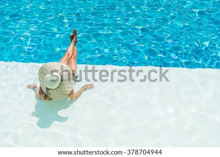 Young woman sitting on the ledge of the swimming pool. - stock photo
