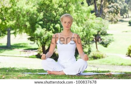 Young woman sitting on the meadow in yoga position