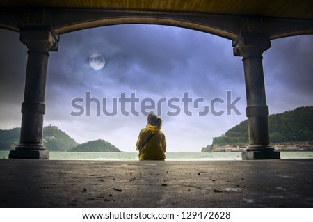 Young woman sitting on the promenade in front of San Sebastian beach (in Basque county, Spain) and gazing at the moon in a cloudy sky - stock photo