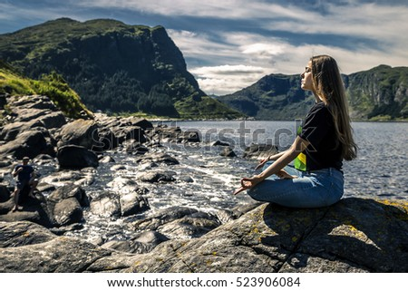 Young woman sitting on the rocks, Norway