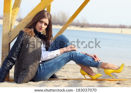 Young woman sitting on the sand - stock photo