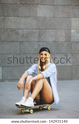 Young woman sitting on the skater / Smiling woman with skateboard in outdoors