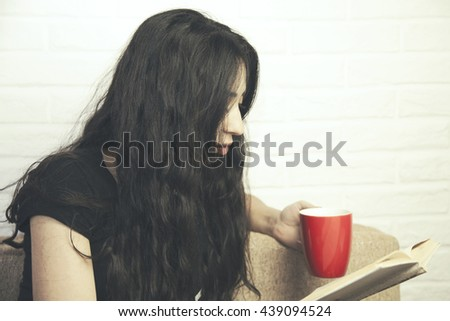 Young woman sitting on the sofa with a cup and a book in her hands