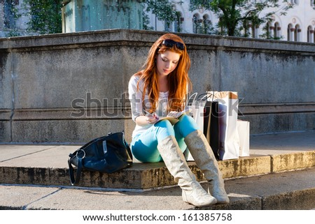 Young woman sitting on the steps of a fountain, besides her are shopping bags