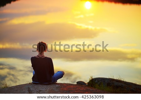 Young woman sitting on the stone enjoying peaceful moment of sunset. In the reflection of the lake water sees clouds and sun. - stock photo