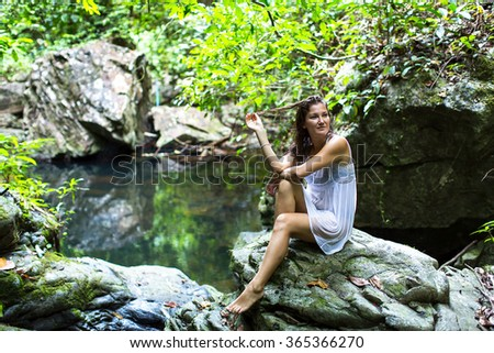 Young woman sitting on the stones near the forest waterfall pond.