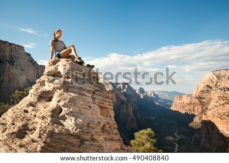 Young woman sitting on the top of mountain, Zion National Park, Utah, USA