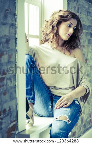 Young woman sitting on the window sill - stock photo