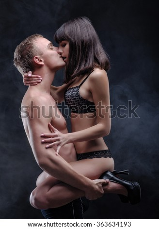 Young woman sitting on the young man kisses him. Both of them in lingerie. Scene in the dark with fog on background.