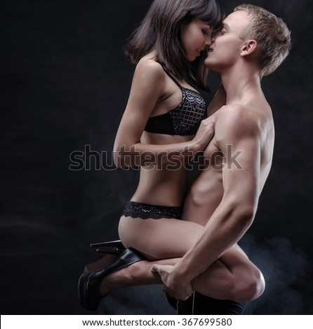 Young woman sitting on the young man kisses him. Both of them in lingerie. Scene in the dark with fog on background. - stock photo