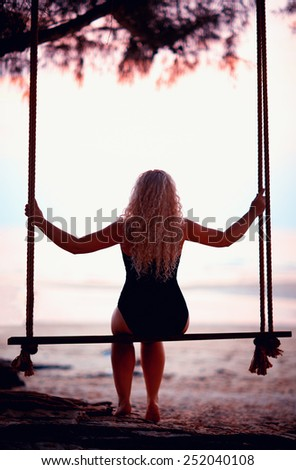 young woman sitting on tree wings at the beach - stock photo
