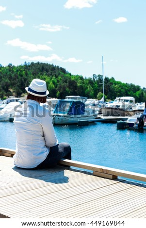 Young woman sitting on wood pier in harbor, alone, looking at horizon