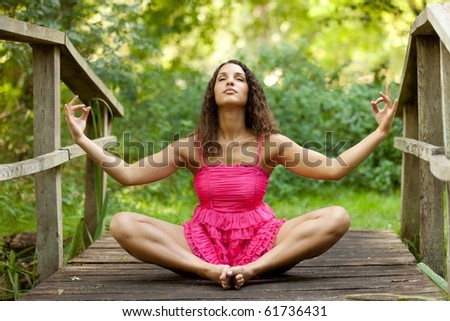 young woman sitting on wooden bridge in lotus position