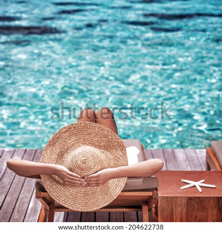Young woman sitting on wooden pier on the sea wearing hat and taking sun bath, enjoying perfect summer day, traveling and luxury vacation concept - stock photo