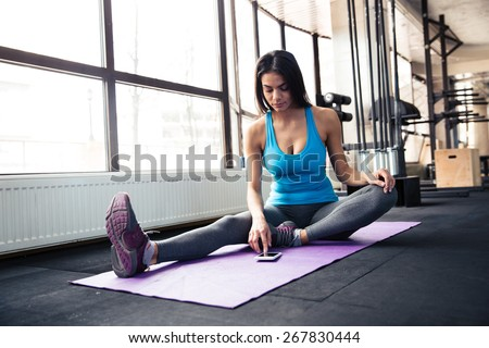 Young woman sitting on yoga mat and using smartphone at gym - stock photo