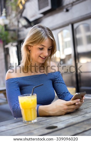 young woman sitting outside a bar with a orange juice and phone - stock photo