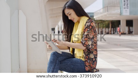Young woman sitting reading her tablet