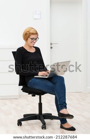 Young woman sitting typing on her laptop on an office chair in the middle of an empty newly painted white room as she waits for her furniture to arrive - stock photo
