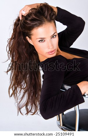 young woman sitting with hand in hair