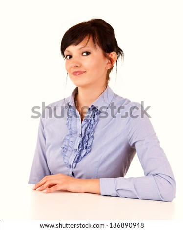 young woman sitting with hand on the table, white background - stock photo