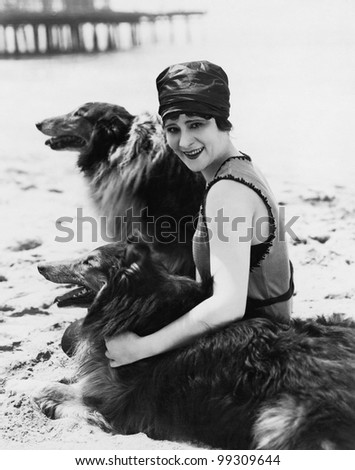 Young woman sitting with her Collies on the beach - stock photo