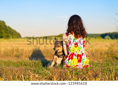 Young woman sitting with her dog on the meadow at sunset - stock photo