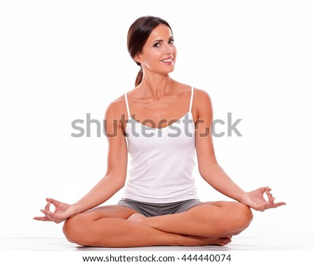 Young woman sitting with her legs crossed while looking at camera with a toothy smile and wearing a white tank top and gray shorts isolated