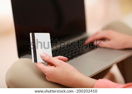 Young woman sitting with laptop and holding credit card - stock photo