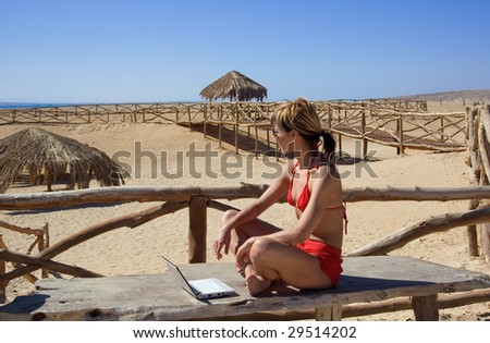 Young woman sitting with notebook in sunny resort - stock photo