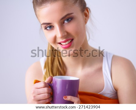 Young woman sitting with pillow and holding a cup of tea.