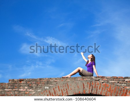 Young woman sitting with raised hand against blue sky - stock photo