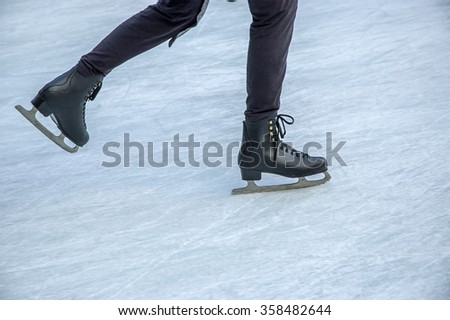 Young woman skating on ice. Ice skates as a detail