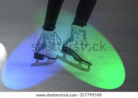 Young woman skating on ice with colorful light show. Ice skates as a detail   - stock photo