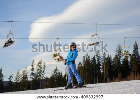Young woman skier against ski-lift and forest on a sunny day. Girl is wearing helmet skiing glasses, gloves and blue ski suit. Ski resort at Carpathian Mountains, Bukovel, Ukraine