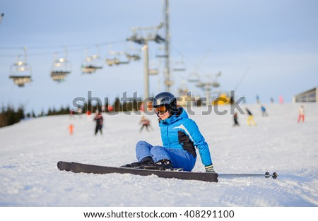 Young woman skier in blue ski suit getting up after the fall on mountain slope against ski-lift. Ski resort at Carpathian Mountains, Bukovel. Winter sports concept. - stock photo