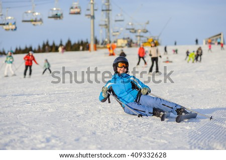 Young woman skier in blue ski suit smiling after the fall on mountain slope. Winter sports concept. Ski resort at Carpathian Mountains - stock photo