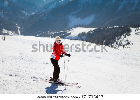Young woman skier standing on snowy hillside
