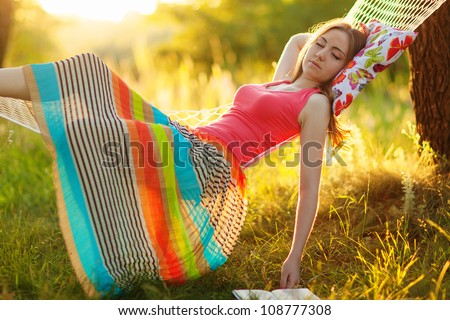 Young woman sleeping in a hammock in garden - stock photo