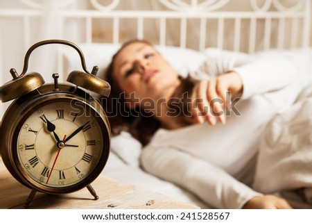 Young woman sleeping in bed beside alarm clock