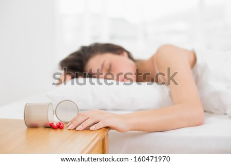 Young woman sleeping in bed by bottle of pills on table at home