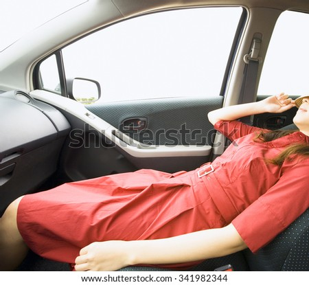 Young woman sleeping in car - stock photo