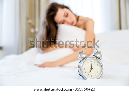 Young woman sleeping in the morning in her bedroom. Focus on alarm - stock photo