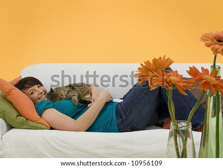 young woman sleeping on a sofa with a little cat - stock photo