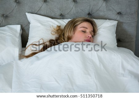 Young woman sleeping on her bed in bedroom at home