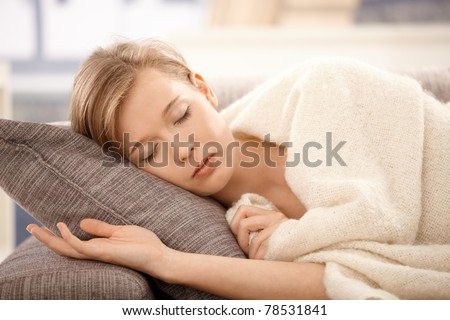Young woman sleeping on sofa at home, covered with blanket.? - stock photo
