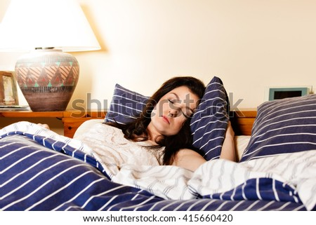 Young woman sleeping on the white bed-clothes in bed at home
