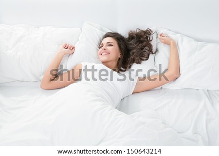 young woman sleeping on the white linen in bed at home, top view - stock photo