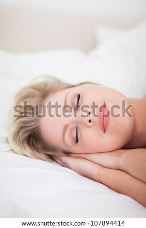 Young woman sleeping with make up on her face on her bed