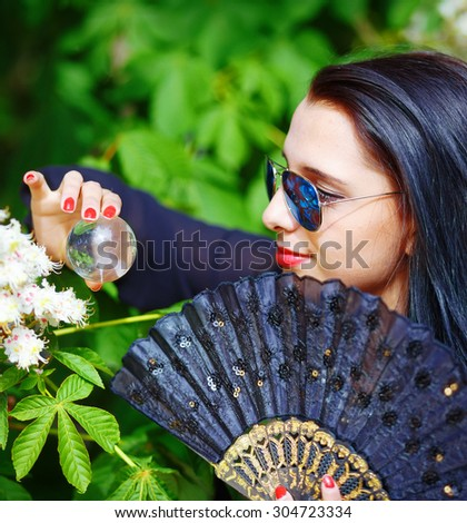 Young woman smelling a beautiful sakura blossom, purple flowers. Spring Magic, Magical Glass sphere in hand and beautiful ornamental fan. Flower background